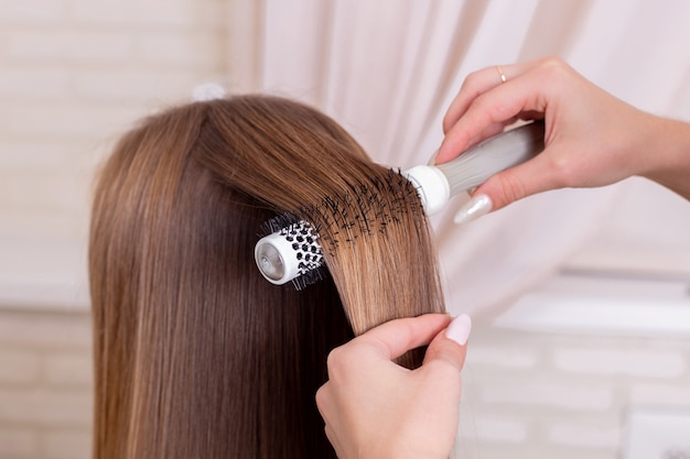 Hairdresser's hands brushing long brunette hair Premium Photo