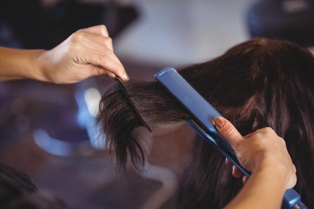 クライアントの髪を整える美容師 Premium写真