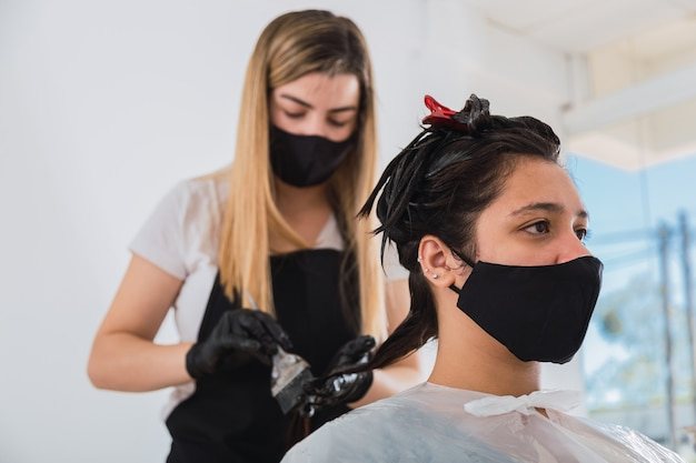 고객에게 염료를 적용하는 얼굴 마스크와 장갑을 가진 미용사 프리미엄 사진