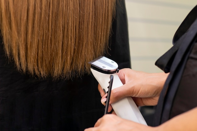 Hairdresser with a hair machine cutting off split ends Premium Photo