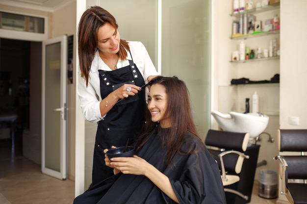 미용사는 미용실의 거울에서 여성 고객의 머리카락과 함께 작동합니다. 헤어 살롱의 스타일리스트와 클라이언트. 뷰티 사업, 전문 서비스 프리미엄 사진