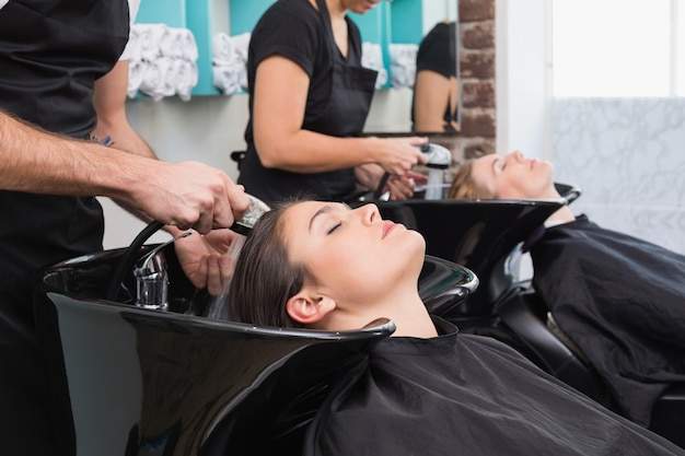 Hairdressers washing their clients hair Premium Photo
