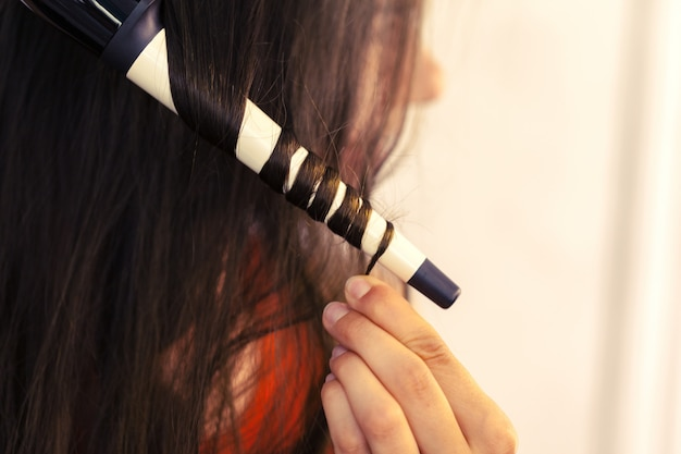 Hairstylist curling hair client in hairdressing salon Premium Photo