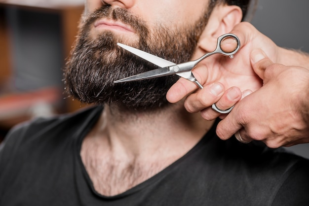Hairstylist's hand cutting man's beard with scissors Free Photo