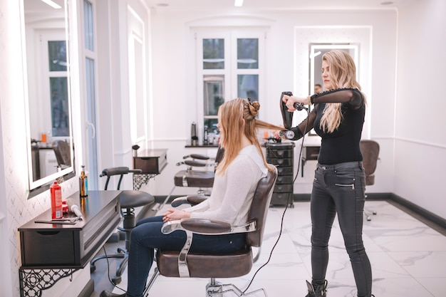 Hairstylist taking care of girl in salon Free Photo