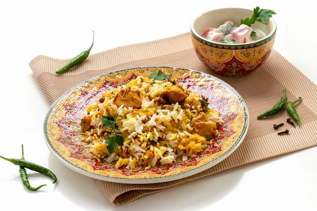 Halal indian chicken biryani served with yogurt tomato raita Premium Photo