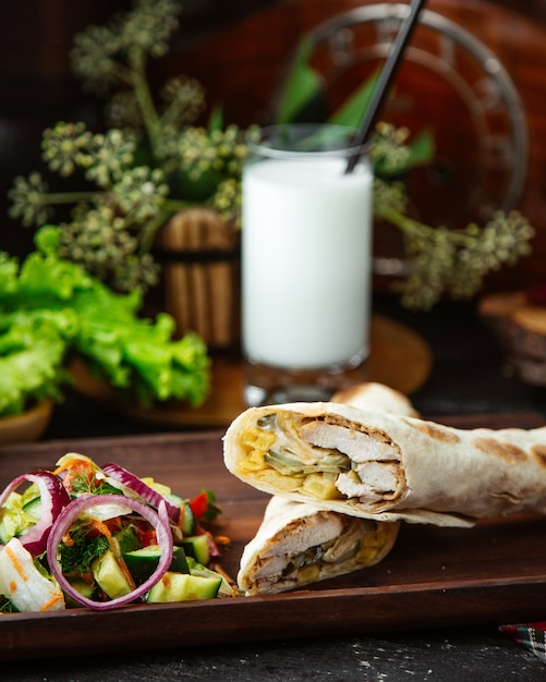 Half cut chicken shawarma served with vegetable salad Free Photo