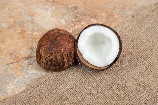 Noci di cocco mature tagliate a metà sulla superficie di marmo con tela. Foto Gratuite