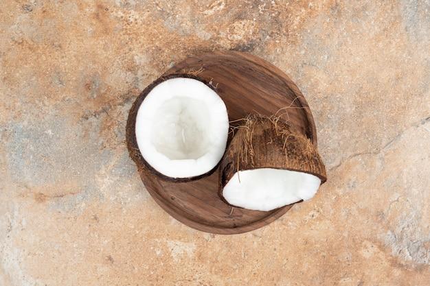 Noci di cocco mature tagliate a metà sul piatto di legno. Foto Gratuite