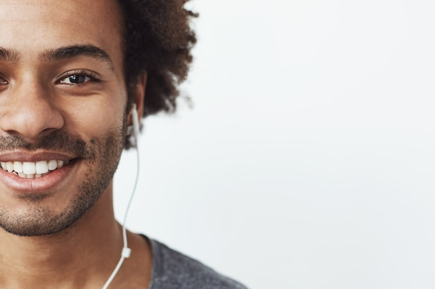 Half face portrait of happy africn man in headphones smiling. Free Photo