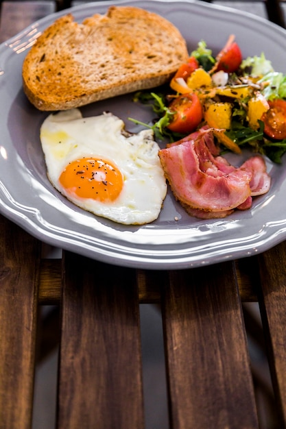 Half fried egg; toast; salad; bacon on gray ceramic plate on wooden table Free Photo