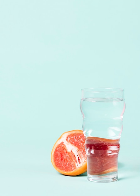 Half of grapefruit with glass of water Free Photo