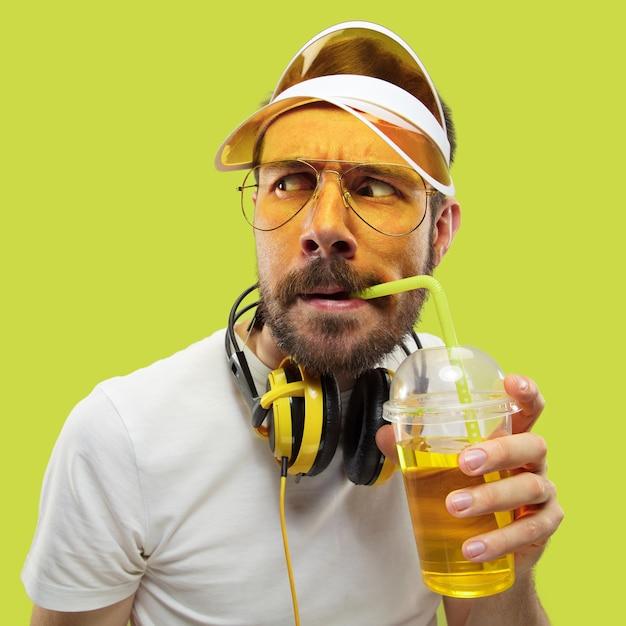 シャツを着た若い男のハーフレングスのクローズアップの肖像画。ヘッドフォンと飲み物を持つ男性モデル。人間の感情、表情、夏、週末のコンセプト。尋ねて見る。 無料写真