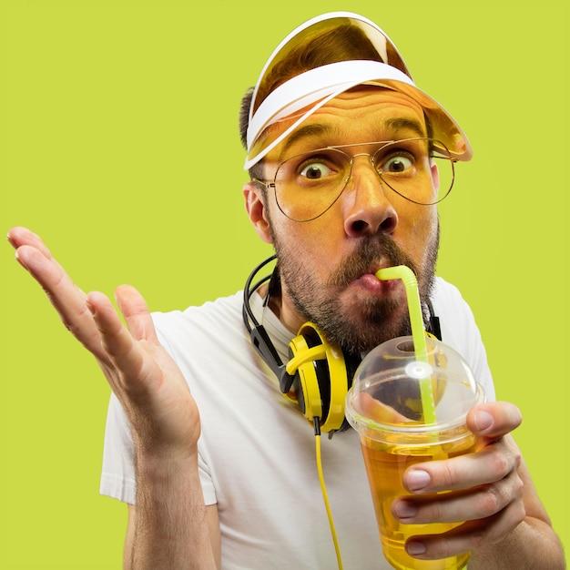 Поясной конец вверх по портрету молодого человека в рубашке. мужская модель с наушниками и напитком. человеческие эмоции, выражение лица, лето, концепция выходных. пить смешно. Бесплатные Фотографии