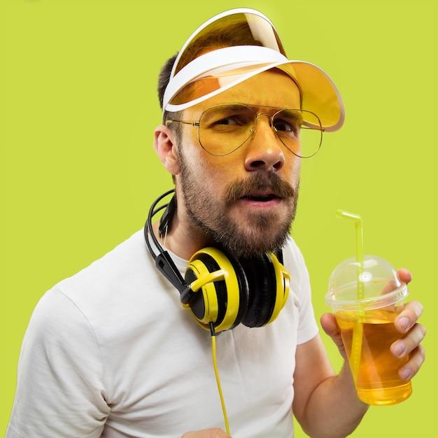シャツを着た若い男のハーフレングスのクローズアップの肖像画。ヘッドフォンと飲み物を持つ男性モデル。人間の感情、表情、夏、週末のコンセプト。真剣になります。 無料写真