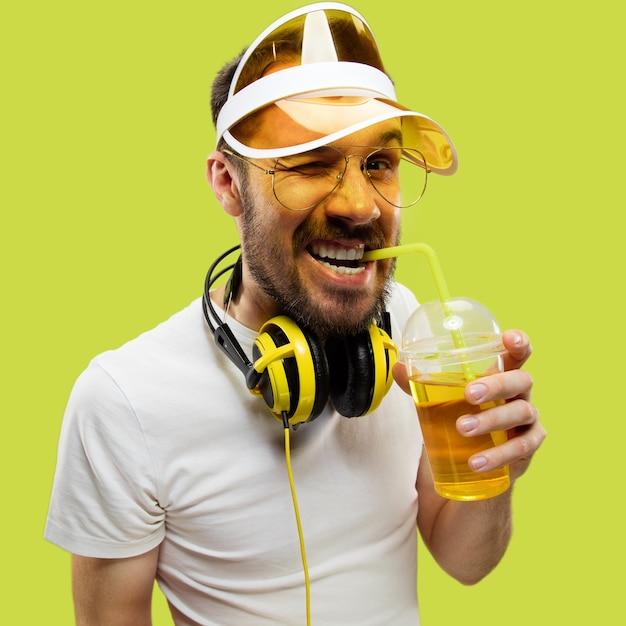 シャツを着た若い男のハーフレングスのクローズアップの肖像画。ヘッドフォンと飲み物を持つ男性モデル。人間の感情、表情、夏、週末のコンセプト。笑顔と飲酒。 無料写真
