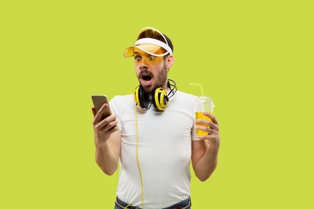 Поясной крупным планом портрет молодого человека в рубашке на желтом пространстве. мужская модель с наушниками и напитком. Бесплатные Фотографии