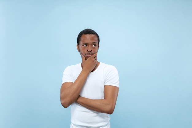 Half-length close up portrait of young african-american man in white shirt on blue wall. human emotions, facial expression, ad concept. thoughtful, thinking covering face with his hands. Free Photo