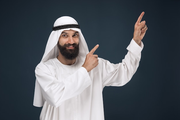 Half-length portrait of arabian saudi businessman on dark blue studio background. young male model smiling and pointing or choosing. concept of business, finance, facial expression, human emotions. Free Photo