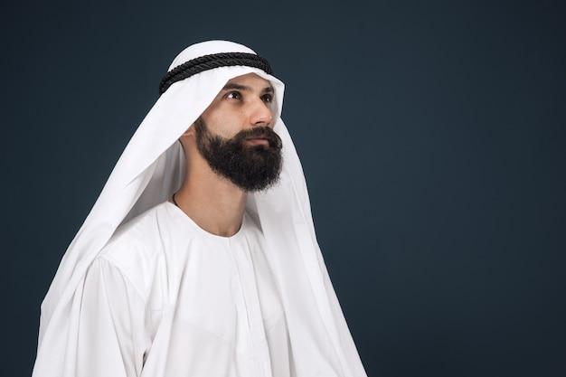 Ritratto a mezzo busto dell'uomo d'affari arabo saudita sulla parete blu scuro. giovane modello maschio in piedi e sembra pensieroso. concetto di affari, finanza, espressione facciale, emozioni umane. Foto Gratuite