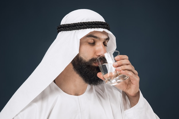진한 파란색 공간에 아라비아 사우디 사업가의 길이 초상화. 젊은 남성 모델 입석 및 식수 무료 사진