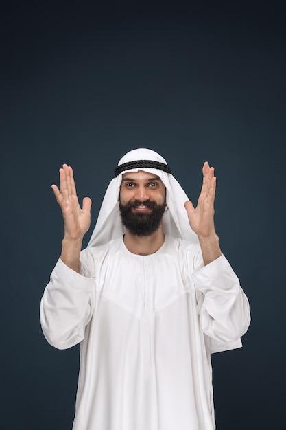 Поясной портрет арабского саудовского бизнесмена на синем пространстве. молодой мужской модели стоя и улыбается Бесплатные Фотографии
