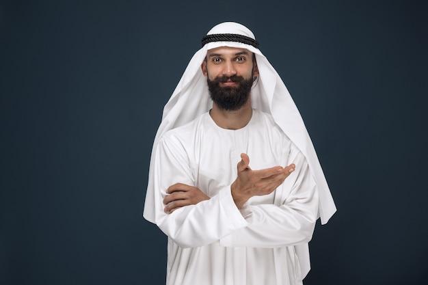 진한 파란색 벽에 아라비아 사우디 사업가의 길이 초상화. 웃 고 가리키는 젊은 남성 모델. 비즈니스, 금융, 표정, 인간 감정의 개념. 무료 사진