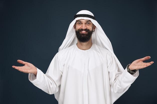 진한 파란색 벽에 아라비아 사우디 사업가의 길이 초상화. 웃 고, 초대의 제스처를 보여주는 젊은 남성 모델. 비즈니스, 금융, 표정, 인간 감정의 개념. 무료 사진