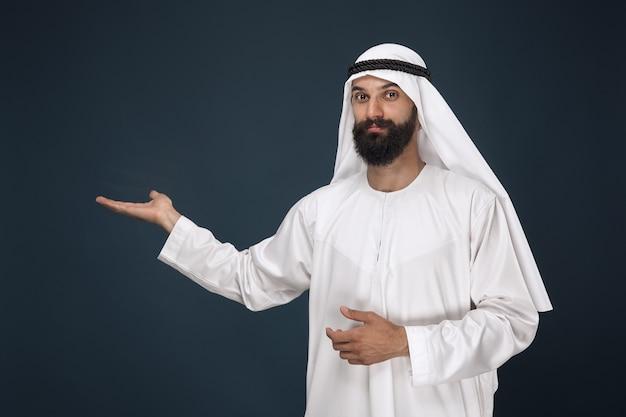 진한 파란색 공간에 아라비아 사우디 남자의 길이 초상화. 웃 고 가리키는 젊은 남성 모델 무료 사진