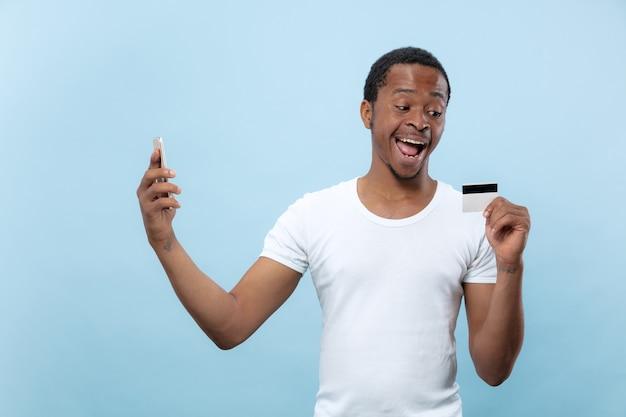 Поясной портрет молодого афро-американского человека в белой рубашке, держащего карту и смартфон на синем фоне. человеческие эмоции, выражение лица, реклама, продажи, финансы, концепция онлайн-платежей. Бесплатные Фотографии