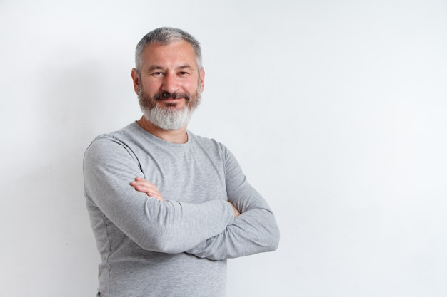Half-length portrait of a serious gray-haired bearded man in a gray t-shirt Premium Photo