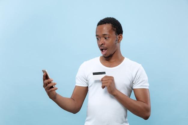 Ritratto a mezzo busto di giovane afro-americano in camicia bianca che tiene una carta e uno smartphone sulla parete blu. emozioni umane, espressione facciale, annuncio, vendite, finanza, concetto di pagamenti online. Foto Gratuite