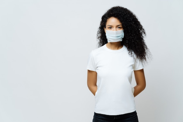 Half length shot of afro american woman being on self isolation or quarantine, wears medical mask during coronavirus outbreak Premium Photo
