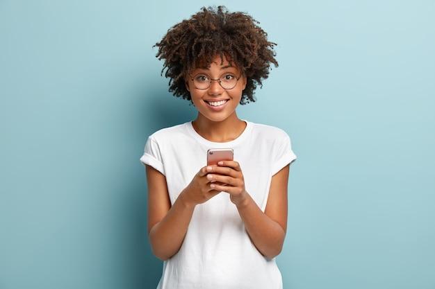 Mezza lunghezza colpo di donna afro tiene il cellulare, gode di belle chiacchiere online nei social network, legge articoli divertenti su internet Foto Gratuite