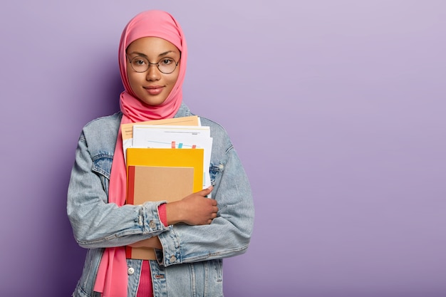 Half length shot of attractive confident muslim college student holds notebooks, paper documents, prepares project work on lesson, wears pink hijab, round spectacles, jean clothes. studying concept Free Photo