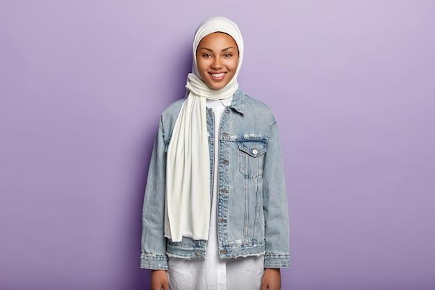 Снимок половинной длины радостной арабской женщины в белом хиджабе и джинсовой куртке Бесплатные Фотографии