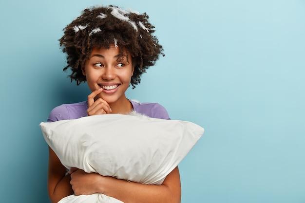 ポジティブな暗い肌の女の子の半分の長さのショットは夢のような表情で見え、口の近くに手を保ち、誠実に微笑み、夜に楽しい夢を見て、枕を保持し、睡眠の準備をし、青で隔離 無料写真