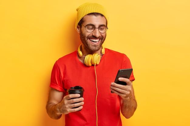 ポジティブな男の半分の長さのショットは、スマートフォンの画面で微笑んで、チャットでオンライン会話をして、すべての問題を忘れています 無料写真