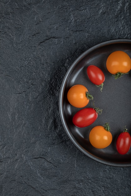 黒の背景に鍋にカラフルなチェリートマトの半分。高品質の写真 無料写真