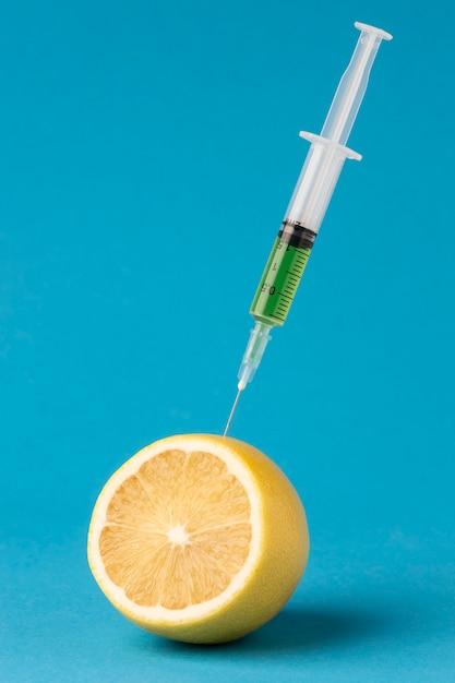 레몬의 절반을 주사기로 주입 프리미엄 사진