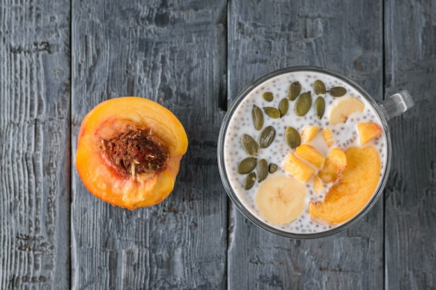 Half peach and pudding with black chia seeds on the village table. the view from the top. flat lay. Premium Photo