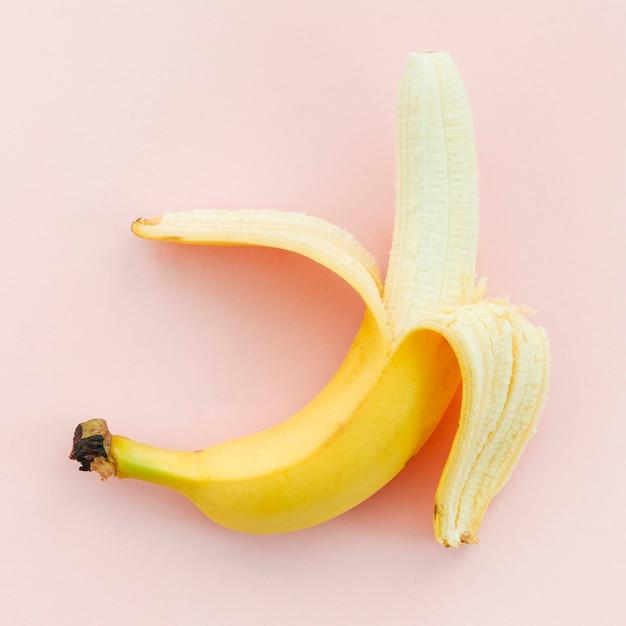 Half-peeled banana on pink background Free Photo