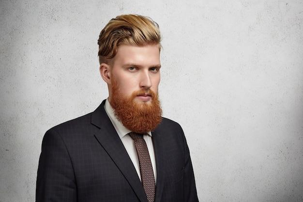 Mezzo profilo di un bel giovane banchiere barbuto in abito classico e cravatta che sembra serio e concentrato in piedi contro il muro grigio con copia spazio per il testo o il contenuto pubblicitario. Foto Gratuite