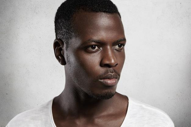 Mezza ripresa di profilo di un giovane africano fiducioso e serio con la pelle pulita e sana, guardando avanti con un'espressione concentrata e determinata. Foto Gratuite
