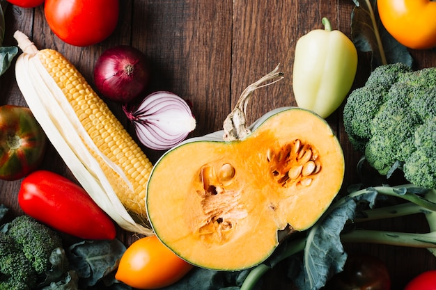 Half of pumpkin surrounded by veggies top view Free Photo