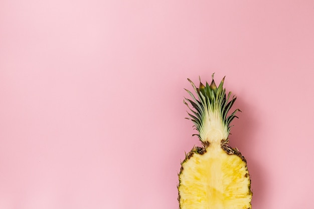 Half slice of beautiful fresh appetizing tasty pineapple on pink background. top view. horizontal. copy space. conceptual. Free Photo