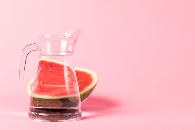 Half sliced watermelon with jug of water Free Photo