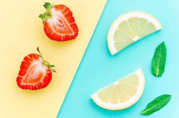 Half strawberries and lemon slices on table Free Photo