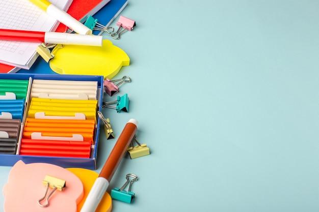 Plastiline colorate con vista a mezza altezza con quaderni sul libro per bambini della scuola di colore blu della parete Foto Gratuite