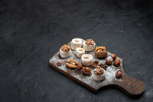 Biscotti diversi di vista a metà superiore con torte e noci sulla superficie grigio scuro torta biscotto zucchero cuocere biscotti dolci Foto Gratuite